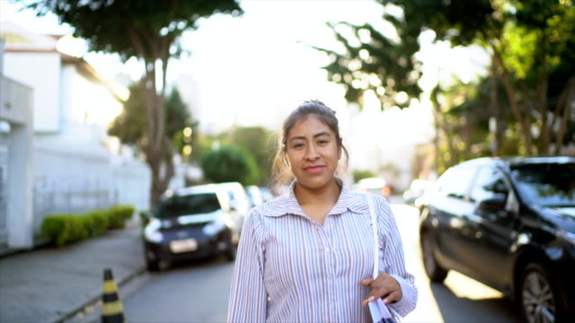 portrait of a latin woman walking in the street - slow motion - peruvian ethnicity stock videos & royalty-free footage