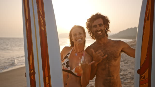 vídeos y material grabado en eventos de stock de retrato de risa surfistas masculinos y femeninos en la playa al atardecer - sin camisa