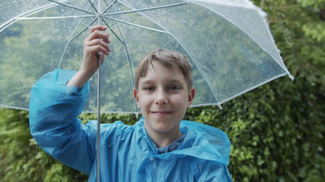portrait of a little boy in the rain - raincoat stock videos & royalty-free footage
