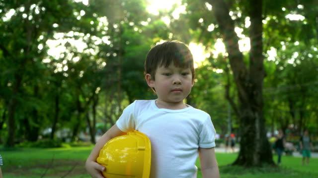 Porträt eines kleinen Jungen mit Schutzhelm. Das Konzept der Immobilien und Engineering.