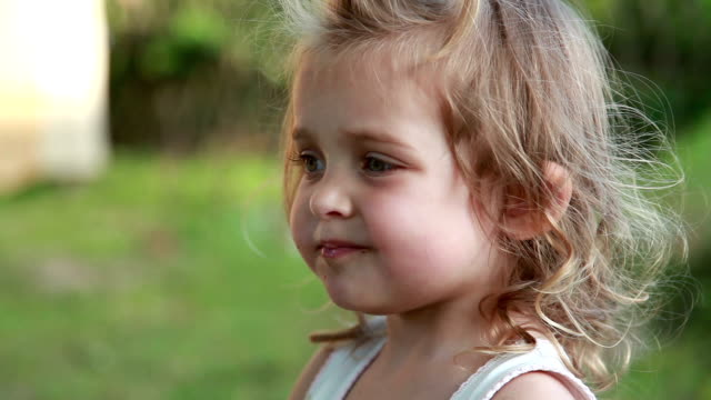 stockvideo's en b-roll-footage met portret van een klein meisje het eten van bessen in de achtertuin - babymeisjes