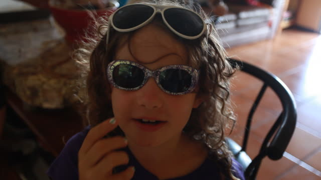 a portrait of a little girl wearing two pairs of glasses and making them work for her. - kelly mason videos stock-videos und b-roll-filmmaterial