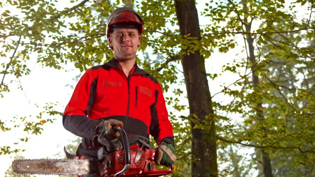 vídeos de stock e filmes b-roll de slo mo ds portrait of a logger holding a chainsaw - one mid adult man only