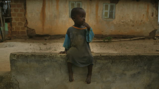 Portrait of a lonely small boy in African village