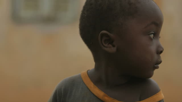 portrait of a lonely small boy in african village - poverty stock videos & royalty-free footage