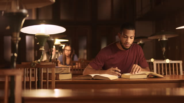 ds portrait of a male african-american student studying in the library - studying stock videos & royalty-free footage