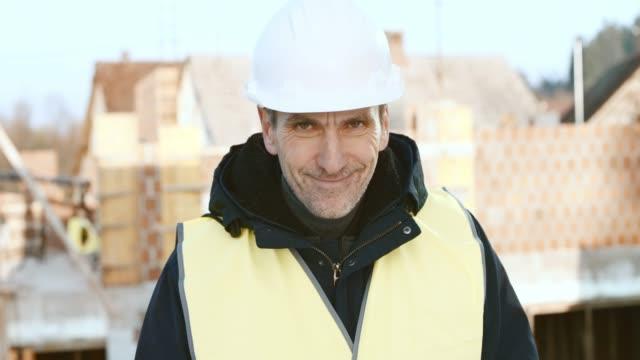 vídeos de stock, filmes e b-roll de retrato de um arquiteto masculino de desenho sobre os planos da construção e sorrindo - plano de arquitetura