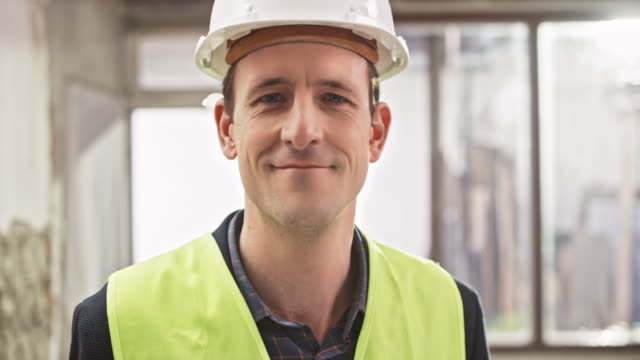 portrait of a male construction manager holding the plans in his hand at the construction site - work helmet stock videos & royalty-free footage
