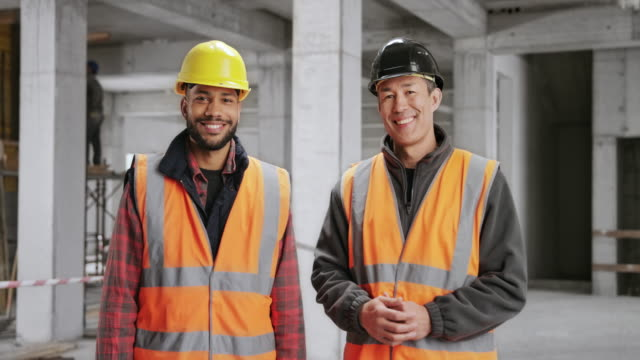 portrait of a male construction worker and a male architect smiling while standing at the construction site - construction worker stock videos & royalty-free footage