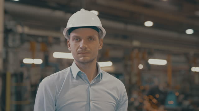 slo mo portrait of a male engineer posing inside the manufacturing plant - foreman stock videos & royalty-free footage