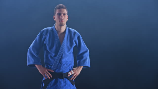 slo mo ds portrait of a male judoist in blue outfit on black background - world sports championship stock videos & royalty-free footage