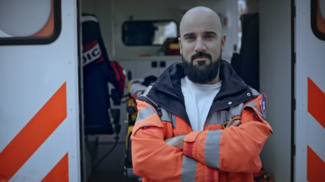 portrait of a male paramedic with a beard standing next to the ambulance - paramedic stock videos & royalty-free footage
