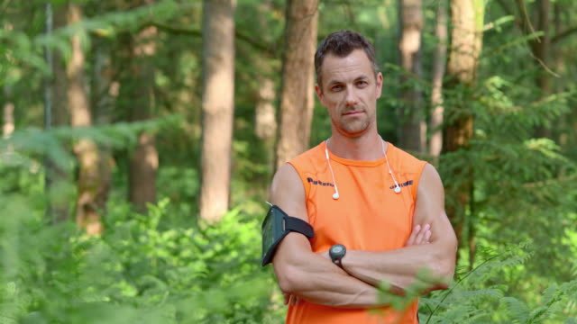 slo mo ds portrait of a male runner in the forest - vest stock videos & royalty-free footage