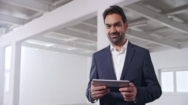 portrait of a male startup investor a digital tablet and smiling while standing in an empty business building - approaching stock videos & royalty-free footage