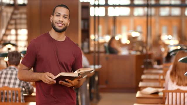 DS Porträt von Studenten Daumen durch ein Buch in der Bibliothek