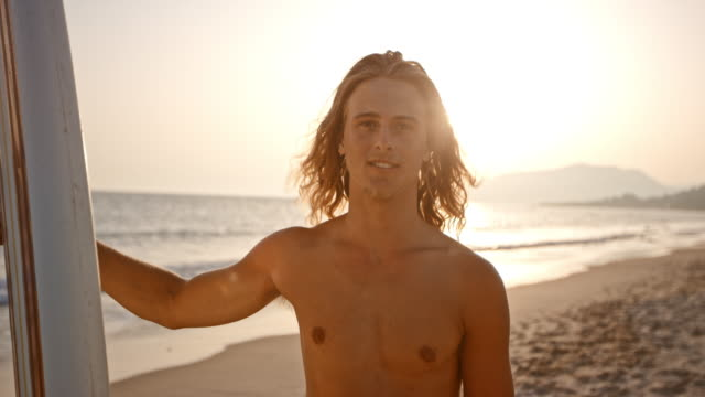 portrait of a male surfer holding his surf board on the beach at sunset - long hair stock videos & royalty-free footage