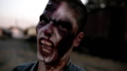 Portrait of a male zombie with bloody teeth and wounded face screaming and shouting. Halloween, filming, staging concept. Blurred railway wagons on the background