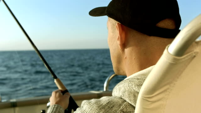 hd: portrait of a man fishing on the boat - fishing reel stock videos and b-roll footage