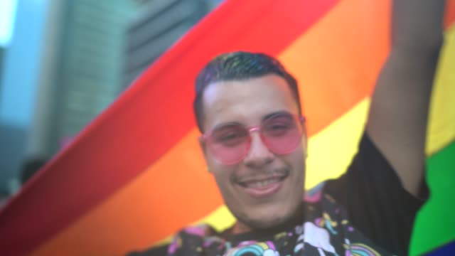 portrait of a man holding rainbow flag during lgbtqi parade - cultura della gioventù video stock e b–roll