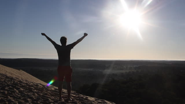 vidéos et rushes de portrait of a man looking at the sun at the top of summit of the pyla dune, a summer morning. against the light - bras en l'air