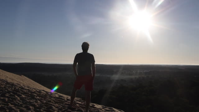 portrait of a man looking at the sun at the top of summit of the pyla dune, a summer morning. against the light - arcachon stock videos & royalty-free footage