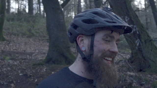 portrait of a man mountain biking in the woods wearing a helmet. - mountainbike bildbanksvideor och videomaterial från bakom kulisserna