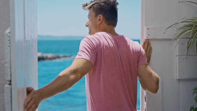 slo mo portrait of a man opening a door of an apartment by the sea - looking at view stock videos & royalty-free footage