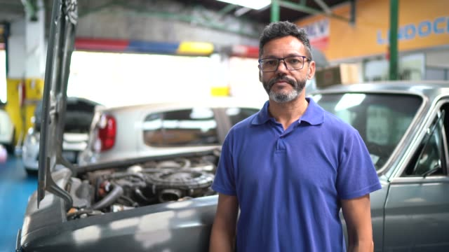 portrait of a man repairing a car in auto repair shop - mechanic stock videos & royalty-free footage