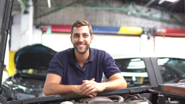 portrait of a man repairing a car in auto repair shop - bonnet stock videos & royalty-free footage