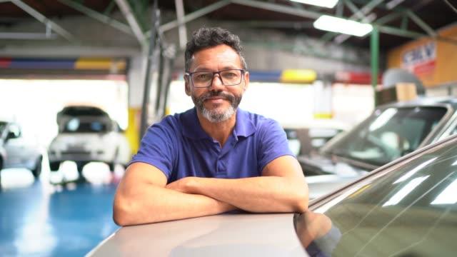 vidéos et rushes de verticale d'un homme réparant une voiture dans l'atelier de réparation d'automobile - réparation
