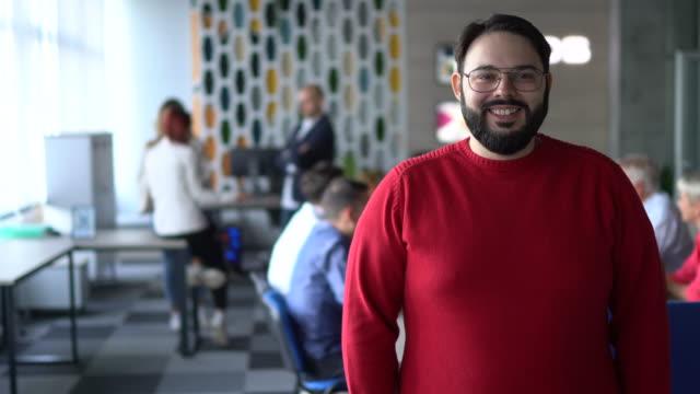 vidéos et rushes de verticale d'un homme restant devant des collègues dans le bureau moderne - barbe