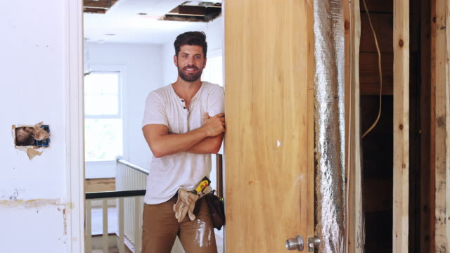 portrait of a man standing in the doorway of his renovation project. - diy stock videos & royalty-free footage