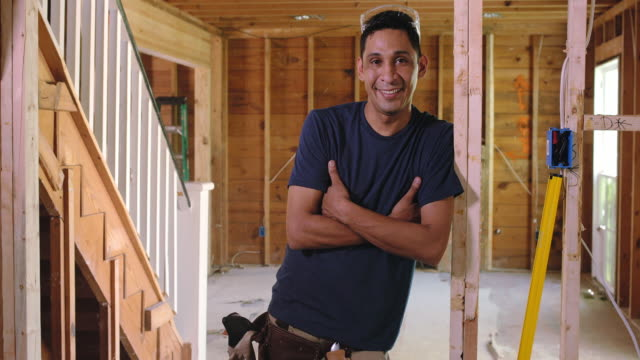Portrait of a man standing with his arms crossed in door frame of renovation project.
