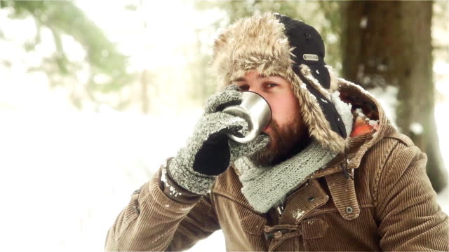portrait of a man taking a rest in snow-capped landscape, bavaria, germany - heißes getränk stock-videos und b-roll-filmmaterial
