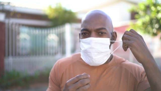 portrait of a man taking face mask off at street - taking off stock videos & royalty-free footage