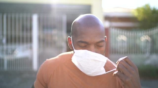 portrait of a man taking face mask off at street - finishing stock videos & royalty-free footage