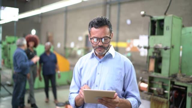 vídeos de stock, filmes e b-roll de retrato de um homem que usa uma tabuleta digital na linha de produção de uma fábrica - indústria eletrônica