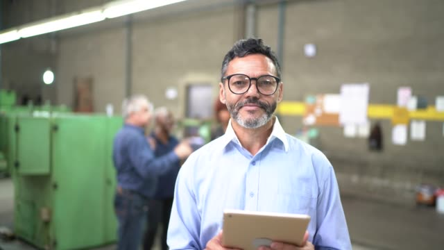 portrait of a man using a digital tablet in the production line of a factory - metal industry stock videos & royalty-free footage