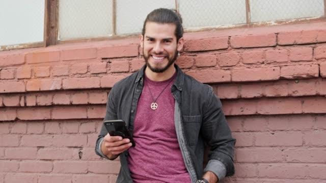 vídeos de stock, filmes e b-roll de retrato de um homem que usa o telefone esperto ao ar livre na frente de uma parede de tijolo - one young man only