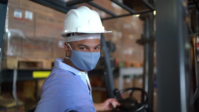 porträt eines mannes mit gesichtsmaske, der einen gabelstapler in einem distributionslager tropft - distribution warehouse stock-videos und b-roll-filmmaterial