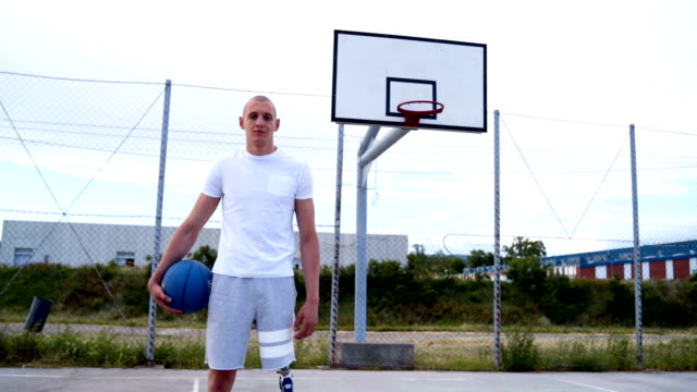 portrait of a man with a prosthetic leg on a basketball court - adaptive athlete stock videos and b-roll footage