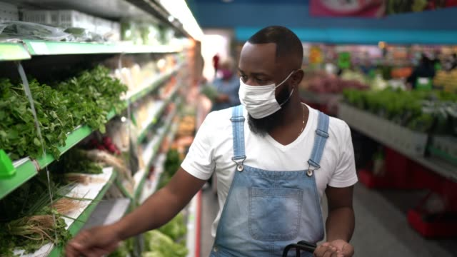 portrait of a man with disposable medical mask shopping in supermarket - leaf vegetable stock videos & royalty-free footage
