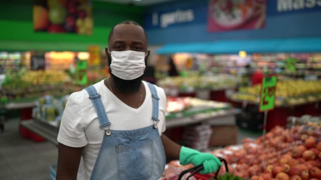 portrait of a man with disposable medical mask shopping in supermarket - pollution mask stock videos & royalty-free footage