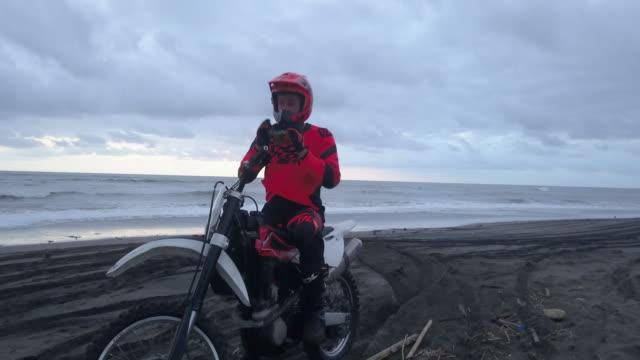 vídeos de stock e filmes b-roll de portrait of a man with his motocross motorcycle on the beach. - risco