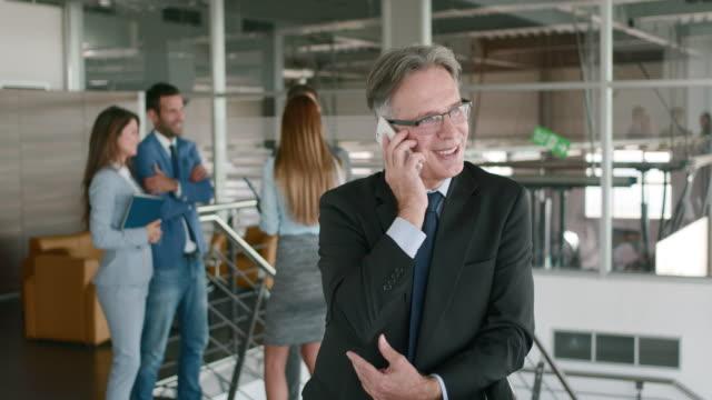 ritratto di un uomo d'affari maturo al telefono con il cliente. - abbigliamento da lavoro formale video stock e b–roll