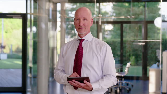 portrait of a mature businessman with a digital tablet in office - formal businesswear stock videos & royalty-free footage