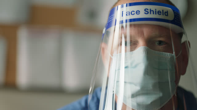 cu portrait of a mature doctor removing his face shield and protective face mask - epidemiology stock videos & royalty-free footage