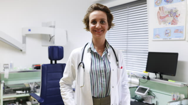 portrait of a mature female doctor standing in her clinic - general practitioner stock videos & royalty-free footage