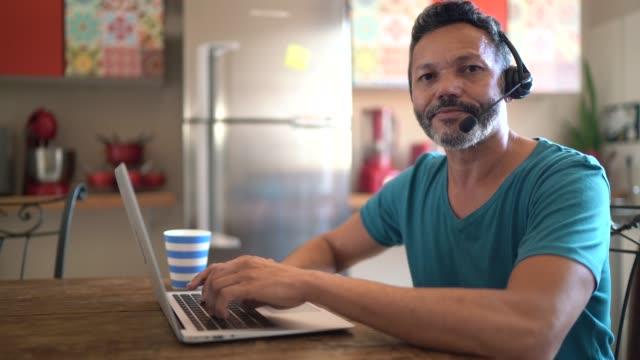 vídeos de stock, filmes e b-roll de retrato de um homem maduro trabalhando em casa, usando fone de ouvido e usando laptop - 50 54 anos