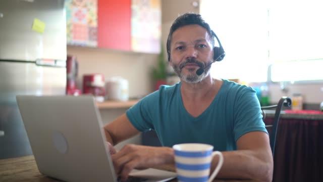 vidéos et rushes de verticale d'un homme mûr travaillant de la maison, utilisant le casque et utilisant l'ordinateur portatif - un seul homme